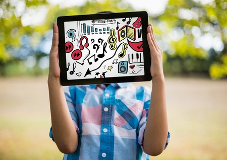 Digital composite of Kid holding tablet over face showing music doodles and white background Stock Photo