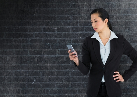 well dressed woman: Digital composite of Businesswoman on phone against dark wall Stock Photo