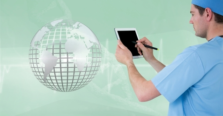 Digital composite of Doctor (men) using his tablet while he looks the 3D metallic earth Stock Photo