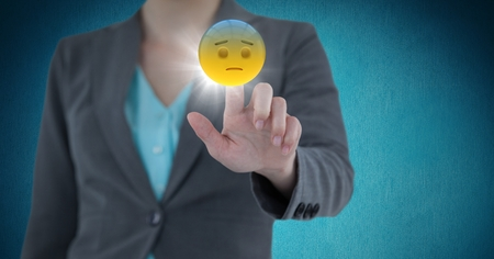 uncomfortable: Digital composite of Business woman mid section touching emojis with flare against blue background