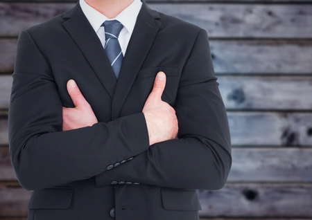 Digital composite of Business man mid section with arms crossed against blurry blue wood panel Stock Photo