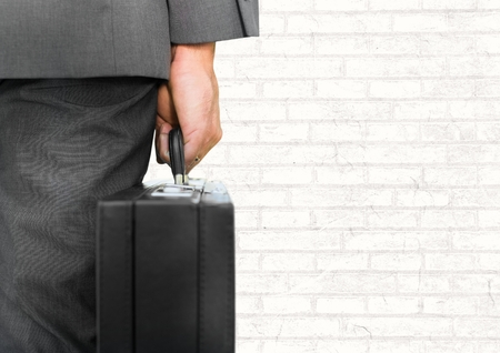 facing: Digital composite of Businessman with briefcase facing white wall Stock Photo