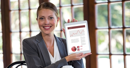 Digital composite of Portrait of happy businesswoman showing graphs on digital tablet