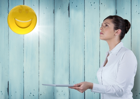 flooring: Digital composite of Business woman with tablet looking up at emoji and flare against blue wood panel