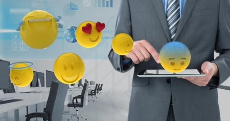 Digital composite of Midsection of businessman using digital tablet with various emojis