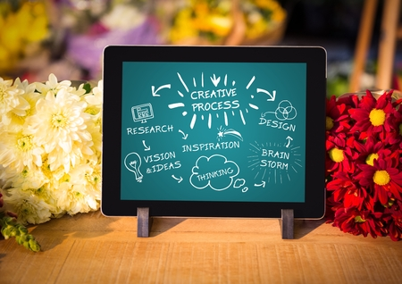 briefing: Digital composite of Tablet on florist table showing white design doodles against teal background