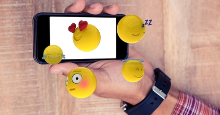 cropped: Digital composite of Digital composite of hand holding smart phone with various emojis
