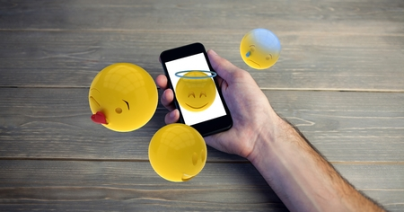 Digital composite of Close-up of hands holding smart phone with various emojis at wooden table Stock Photo