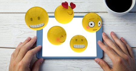 tablet pc in hand: Digital composite of Close-up of hands using digital tablet with various emojis at wooden table