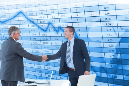 tied in: Digital composite of Happy businessmen shaking hands against stock data background