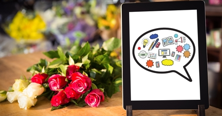 Digital composite of Various icons on digital tablet by flowers on table Stock Photo
