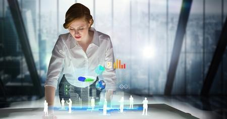 Digital composite of Businesswoman standing at futuristic desk