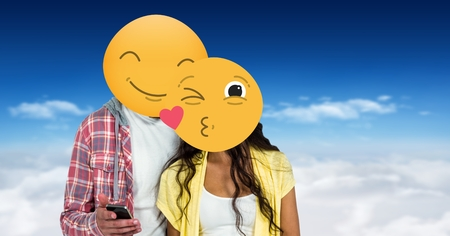 Digital composite of Couple with smiling and kissing emojis on faces using smart phone Stock Photo
