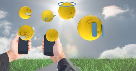 Digital composite of Digitally generated image of emojis flying over hands holding smart phone at field against sky Stock Photo