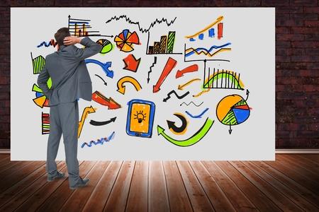floorboards: Digital composite of Digitally generated image of businessman looking at various graphs on billboard against brick wall
