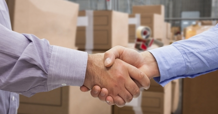 extending: Digital composite of Close-up of business people shaking hands in warehouse
