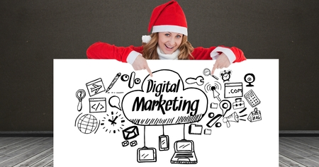 claus: Digital composite of Portrait of happy woman wearing Santa hat showing digital marketing icons on placard Stock Photo