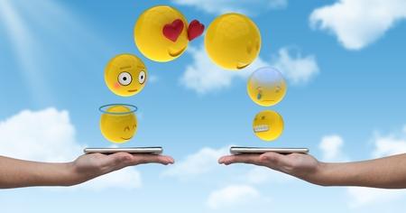 Digital composite of Digitally generated image of emojis flying over hands holding smart phone against sky