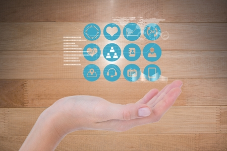 flooring: Digital composite of Digitally generated image of various icons over hand against wooden wall Stock Photo