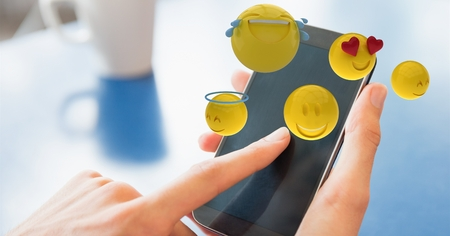 comedor escolar: Compuesto digital de Close-up de manos usando teléfono inteligente con varios emoticones Foto de archivo