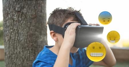 Digital composite of Boy looking at emojis through VR glasses