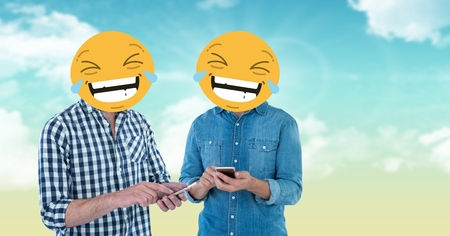 using smart phone: Digital composite of Digital composite of friends with laughing emojis on faces using smart phones Stock Photo