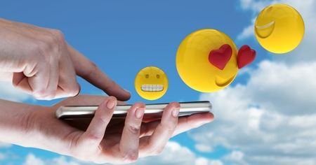Digital composite of Digitally generated image of emojis flying over hands using smart phone against sky Stock Photo
