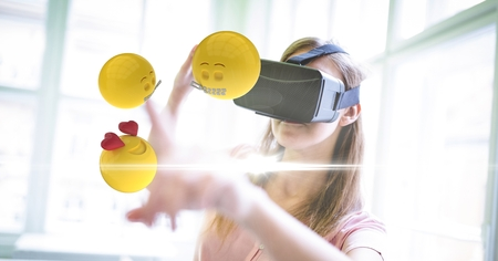 Digital composite of Digitally generated image of emojis flying over against woman using VR glasses at home Stock Photo