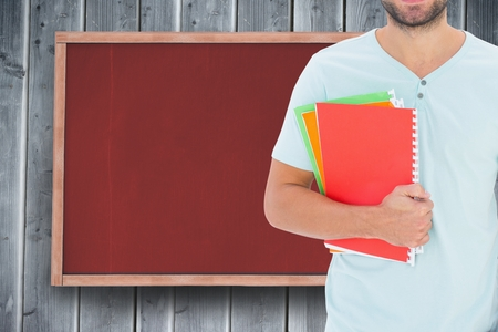 outstretched: Digital composite of Midsection of male college student holding books while standing against notice board Stock Photo