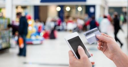 デビット カードで請求書の支払いのためのスマート フォンを使用している人のトリミング画像のデジタル合成 写真素材