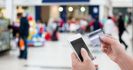 Digital composite of Cropped image of person using smart phone for paying bill through debit card