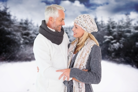 Digital composite of Side view of affectionate senior couple standing at field during winter Stock Photo