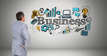 mid adult men: Digital composite of Businessman looking at business text with various icons against gray background