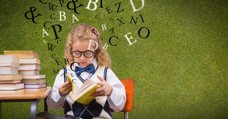 schoolkids: Digital composite of Female student reading book while letters flying in background