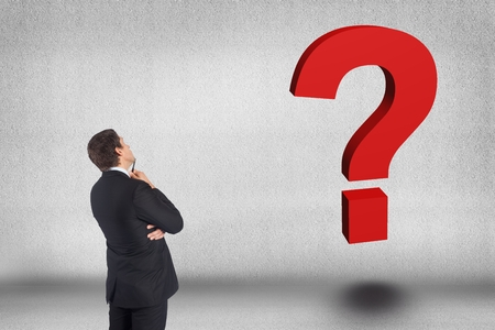 Digital composite of Business man looking question mark against gray background
