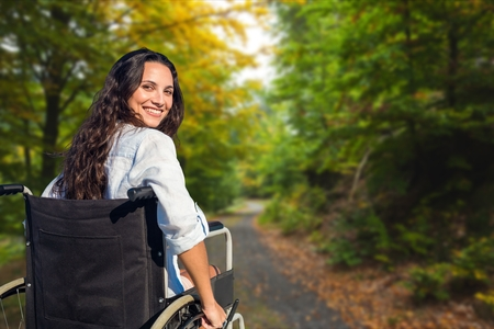 Digital composite of Young woman in wheelchair on street