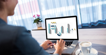 Digital composite of Businesswoman analyzing graphs on laptop at desk