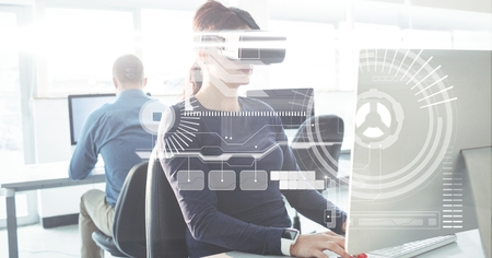 concentrate: Digital composite of Businesswoman wearing VR glasses while using computer in office