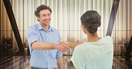 Digital composite of Male and female colleagues shaking hands in office Stock Photo