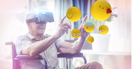 Digital composite of Digitally generated image of emojis flying against man using VR glasses sitting on wheelchair Stock Photo