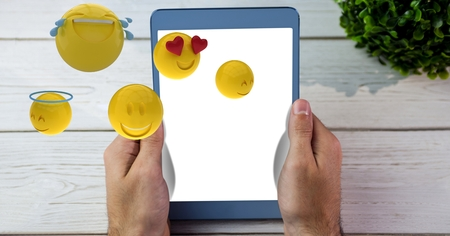 cropped: Digital composite of Hands holding tablet PC while emojis flying over table