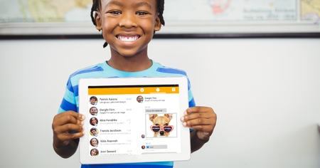 Digital composite of Happy boy showing tablet PC with social site displayed on screen Stock Photo