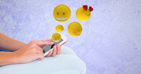 anthropomorphic: Digital composite of Digitally generated image of emojis flying over hands using smart phone