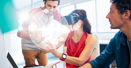 swivel: Digital composite of Businesswoman looking at globe through VR glasses by colleagues Stock Photo