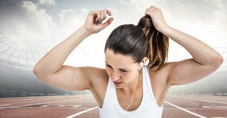 Digital composite of Female runner tying up hair on track against flares