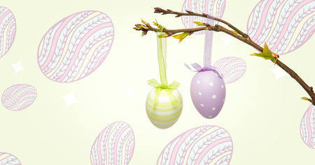arms folded: Digital composite of Easter eggs hanging on branch in front of pattern Stock Photo