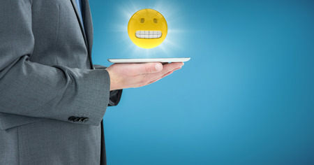 Digital composite of Business man mid section with tablet and emoji with flare against blue backround