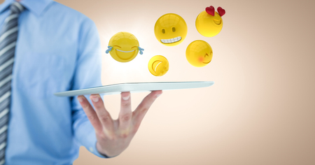 scrolling: Digital composite of Business man mid section holding tablet with one hand and emojis against cream background Stock Photo