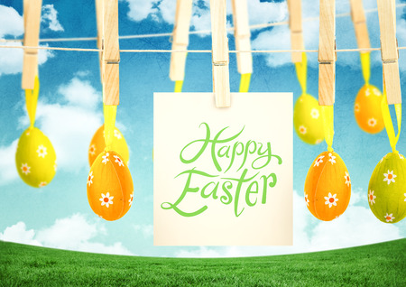 Digital composite of Happy Easter text with Easter Eggs with note on pegs in front of pattern