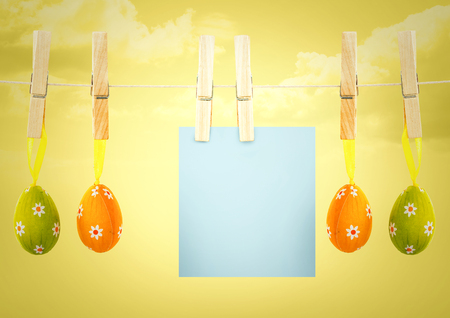 Digital composite of Blue note on washing line with eggs against yellow sky Stock Photo
